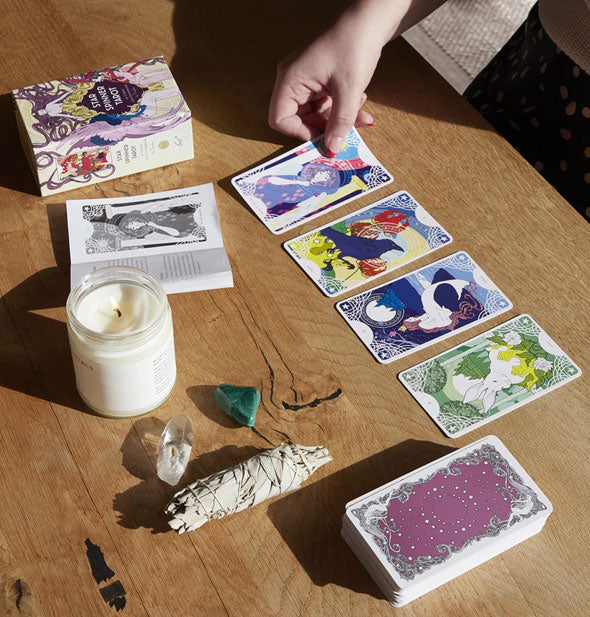 Star Spinner Tarot cards laid out on wooden surface with sage, crystals, and lit candle