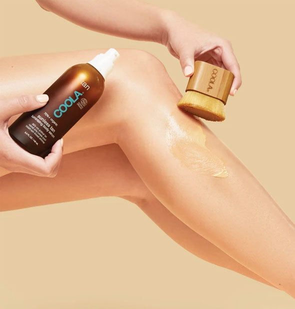 A model applies COOLA Sunless Tan Luminizing Body Serum to leg with a COOLA Kabuki Body Brush