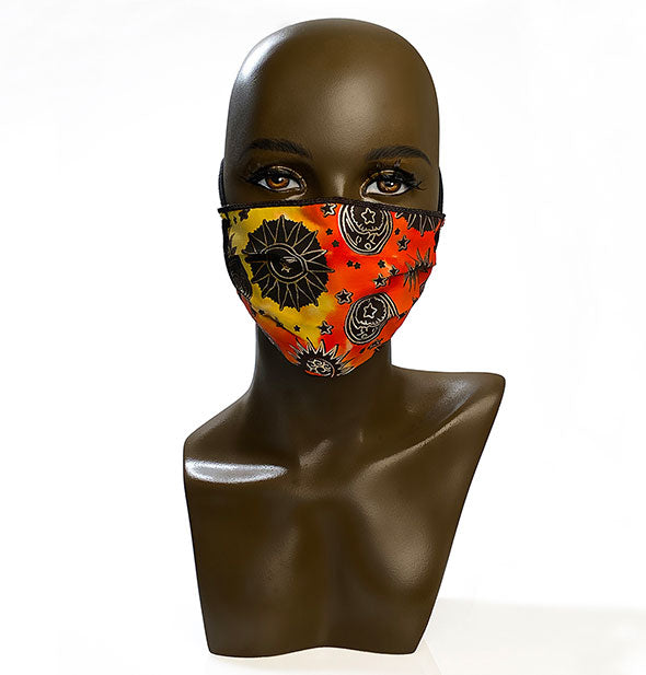 A mannequin head wears a protective face mask with celestial print