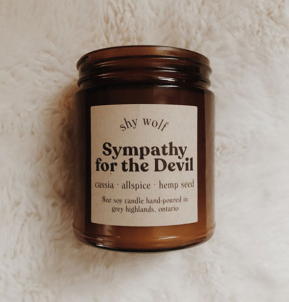Amber glass jar Sympathy for the Devil candle on white fur background