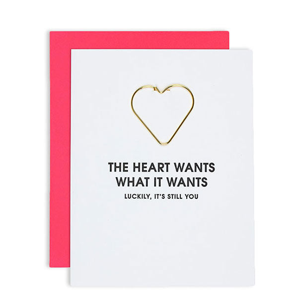 "White greeting card imprinted ""The Heart Wants What It Wants (Luckily It's Still You)"" with gold heart-shaped paper clip attached and red envelope behind."
