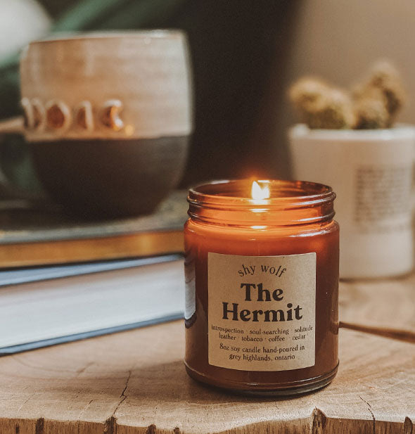 The Hermit amber glass jar candle shown lit on a wooden surface with books and other home goods in the background