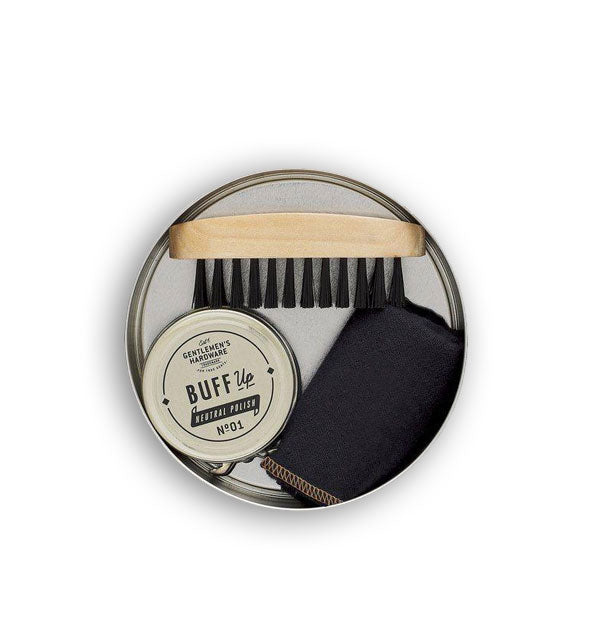 Contents of the Travel Shoe Shine Kit packed inside a round tin: brush, polish, and cloth