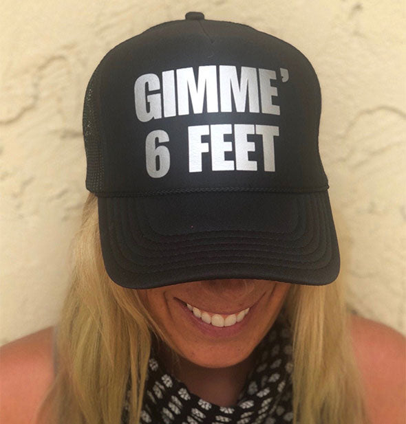 "A model wears a black trucker-style brimmed cap with silver lettering that says, ""Gimme 6 Feet"""