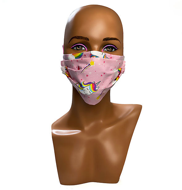 A mannequin head wears a pink unicorn cartoon patterned face mask
