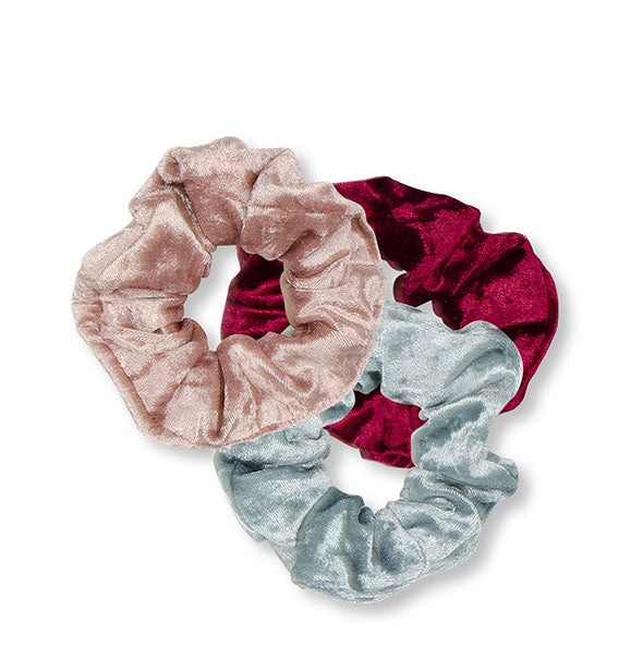 Three velvet hair scrunchies in gray, pink, and red