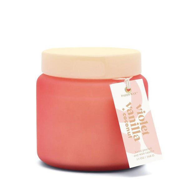 "Coral-colored glass candle jar with cream-colored lid and hangtag that reads, ""Violet Vanilla + Coconut."""