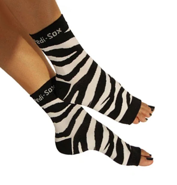 A pair of open-toe zebra print Pedi-Sox socks on a model's feet