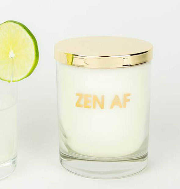 "A glass candle with gold lid is printed with the phrase, ""Zen AF"" in metallic gold foil."