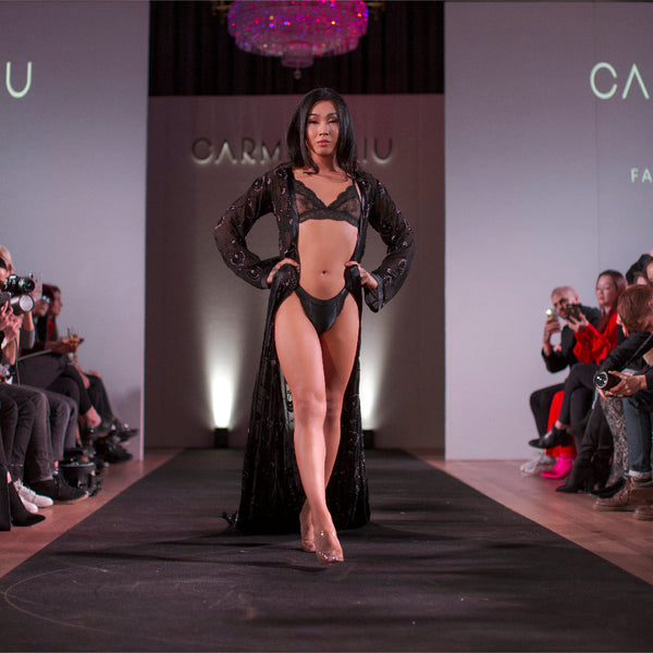 A model in black lingerie and a robe stares forward as they walk down a runway with spectators and photographers on either side.