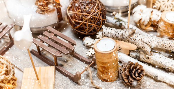 An assorted collection of rustic winter decorations including a small wooden sled, a candle, pinecone, birch branches and more