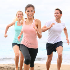 Three friends jogging at the beach and having a good time