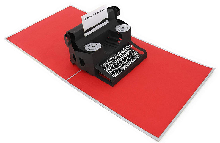 "PopLife pop-up card features mechanical typewriter with ""I love you so much."" message on paper"