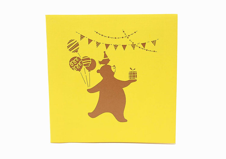 Front cover of card with yellow color features bear with a bird on the head and holding a gift and balloons