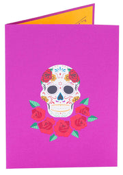 Front cover of card with purple color features colorful sugar skull with flowers