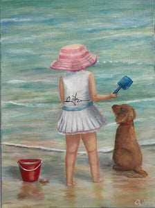 Girl and dog with red bucket on the shore