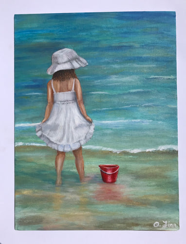 Girl with red bucket on the shore
