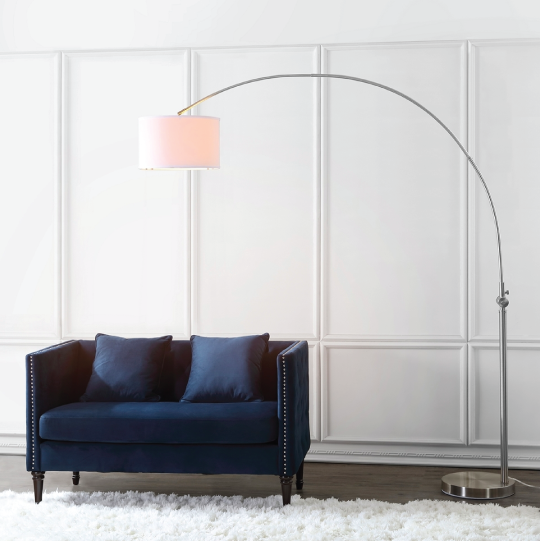 ascella arc floor lamp above blue couch turned on