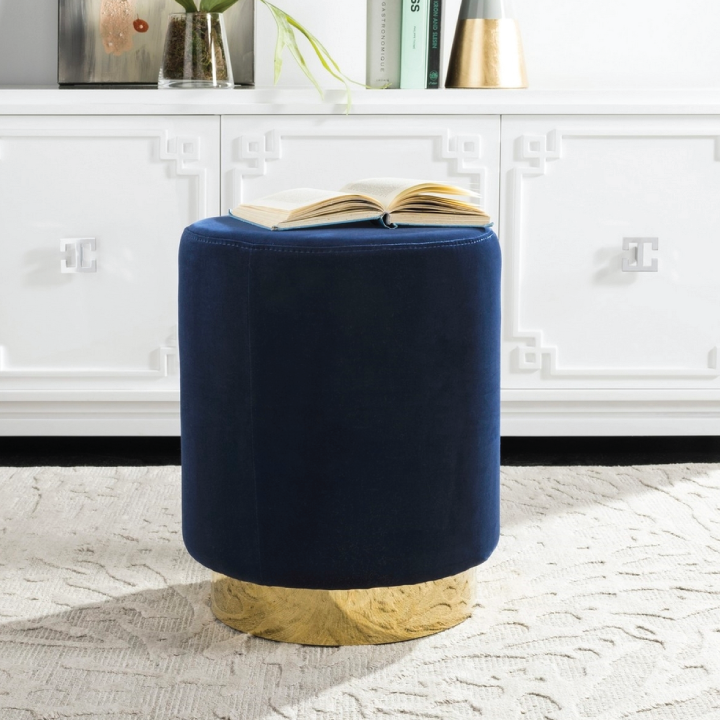 navy blue ottoman with brass base in living space