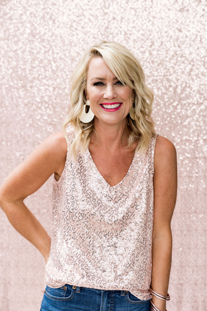 A close up of a beautiful, blonde woman wearing a light pink sequined tank top in front of a light pink backdrop, holiday outfit holiday look