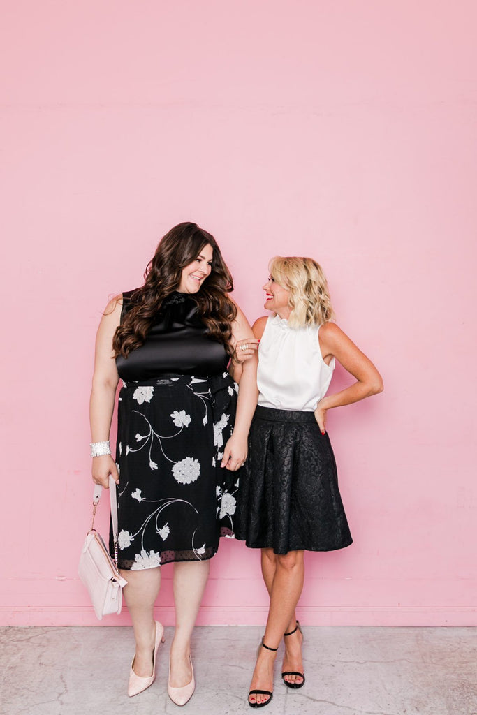 Two women wearing dresses with pink wall in the background.