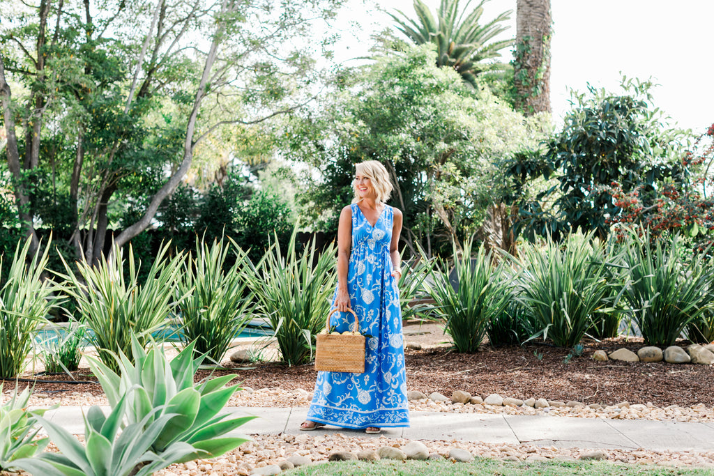 Beautiful blonde woman in flowy blue maxi dress surrounded by plants and palm trees