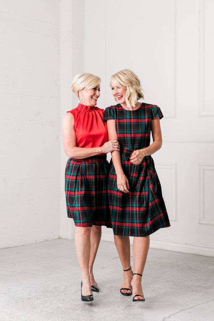 Two beautiful blonde women wearing a plaid dress and a plaid skirt with a red blouse.