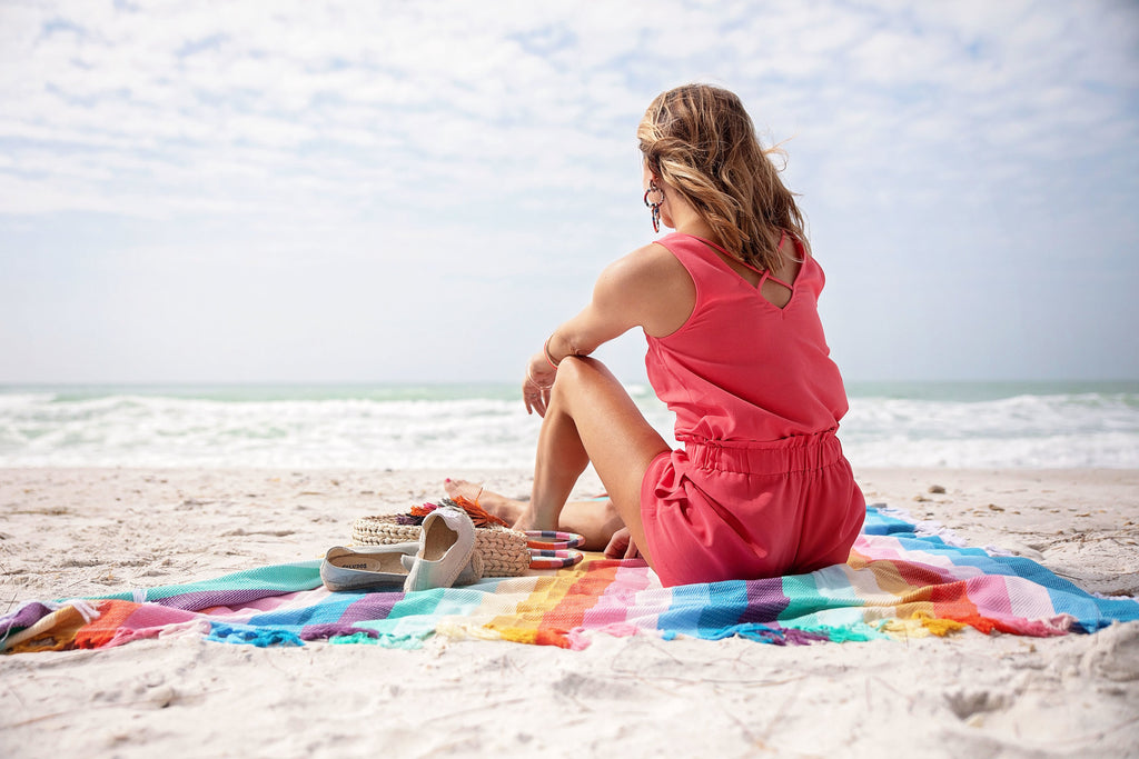 Beautiful tan woman in a coral romper sitting down on a beach towel on the beach staring out into the ocean