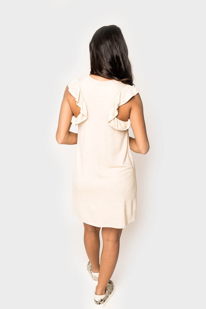 Woman wearing a super soft knit short dress with ruffle trim racerback in color Oatmeal