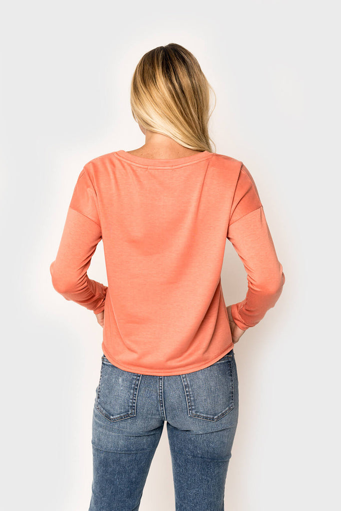 Woman wearing a super soft knit pullover long sleeve sweatshirt in color Apricot