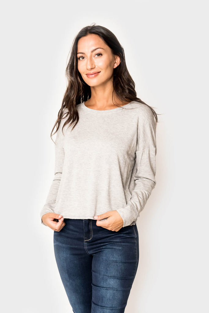 Woman wearing a super soft knit pullover long sleeve sweatshirt in color Heather Grey