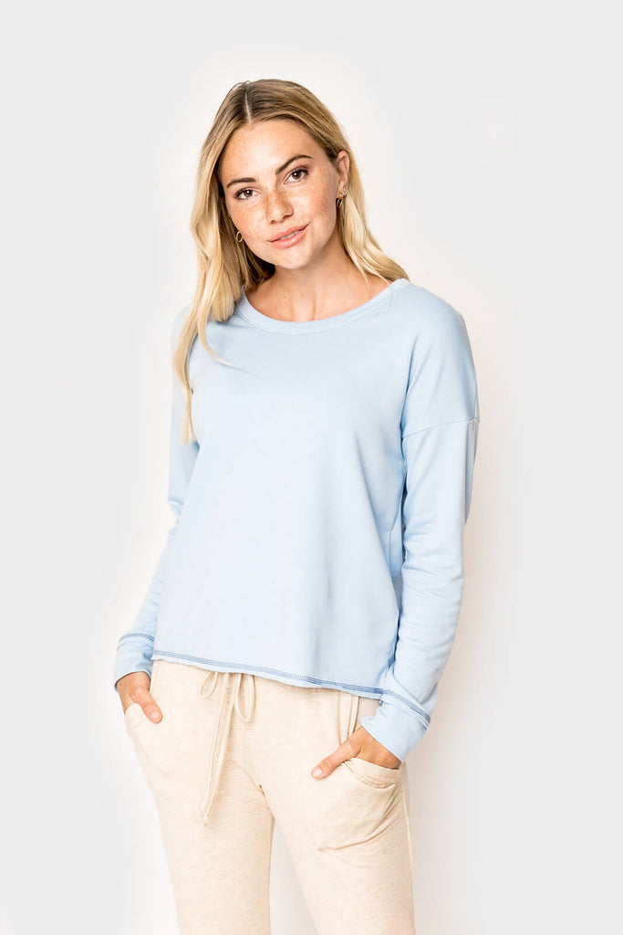 Woman wearing a super soft knit pullover long sleeve sweatshirt in color Ice