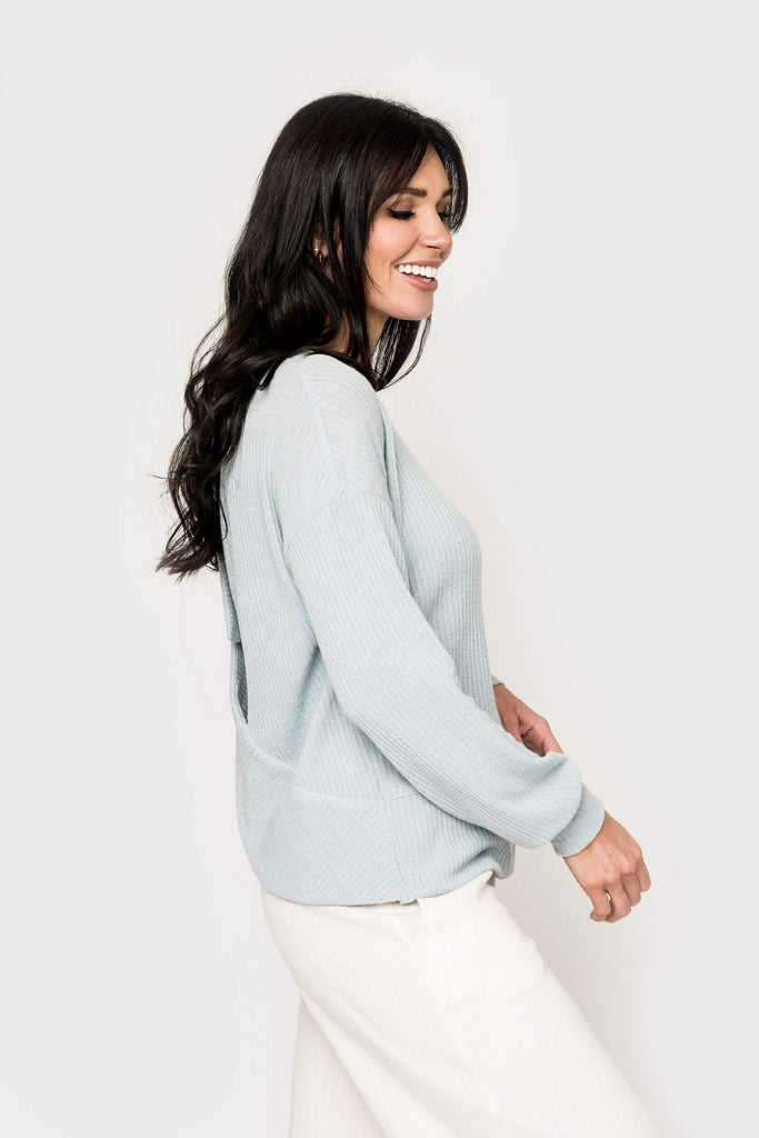 Women wearing With a Twist Wrap Back Sweater Top in chambray