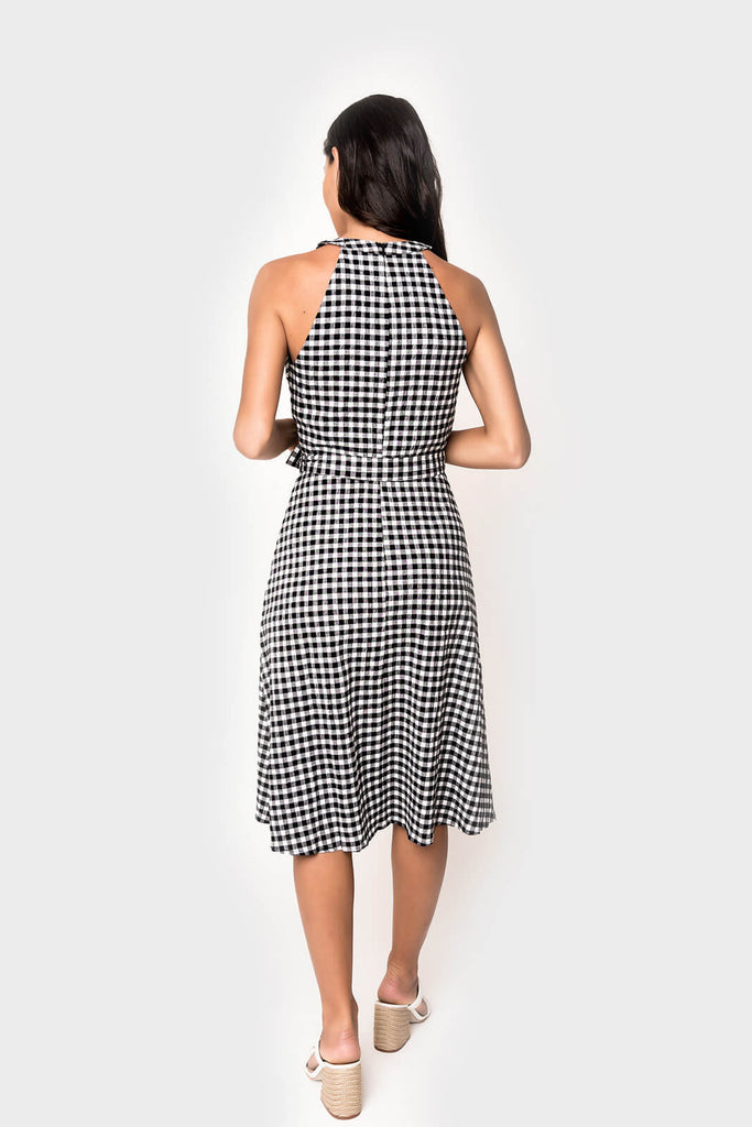 women wearing belted flare halter dress in gingham