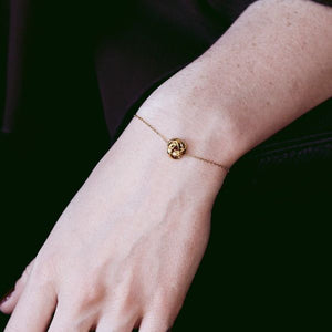 The model is wearing the Gala Bracelet in Gold