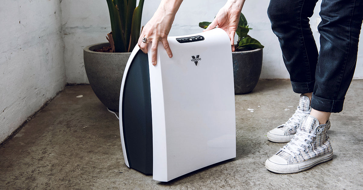 Image of woman wearing sparkly shoes and navy blue pants opening up a Vornado AC350 Air Purifier.