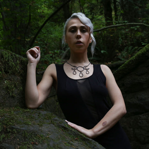 blonde witchy woman fashion strong arms with elbow bend and resting on the rock wall, other arm braces the wall. wearing triple goddess moon necklace at the witches castle in forrest park. Portland, Oregon