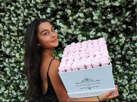 Asal Yusupova of Boite de Luxe posing with the Grand Square boxed arrangement.
