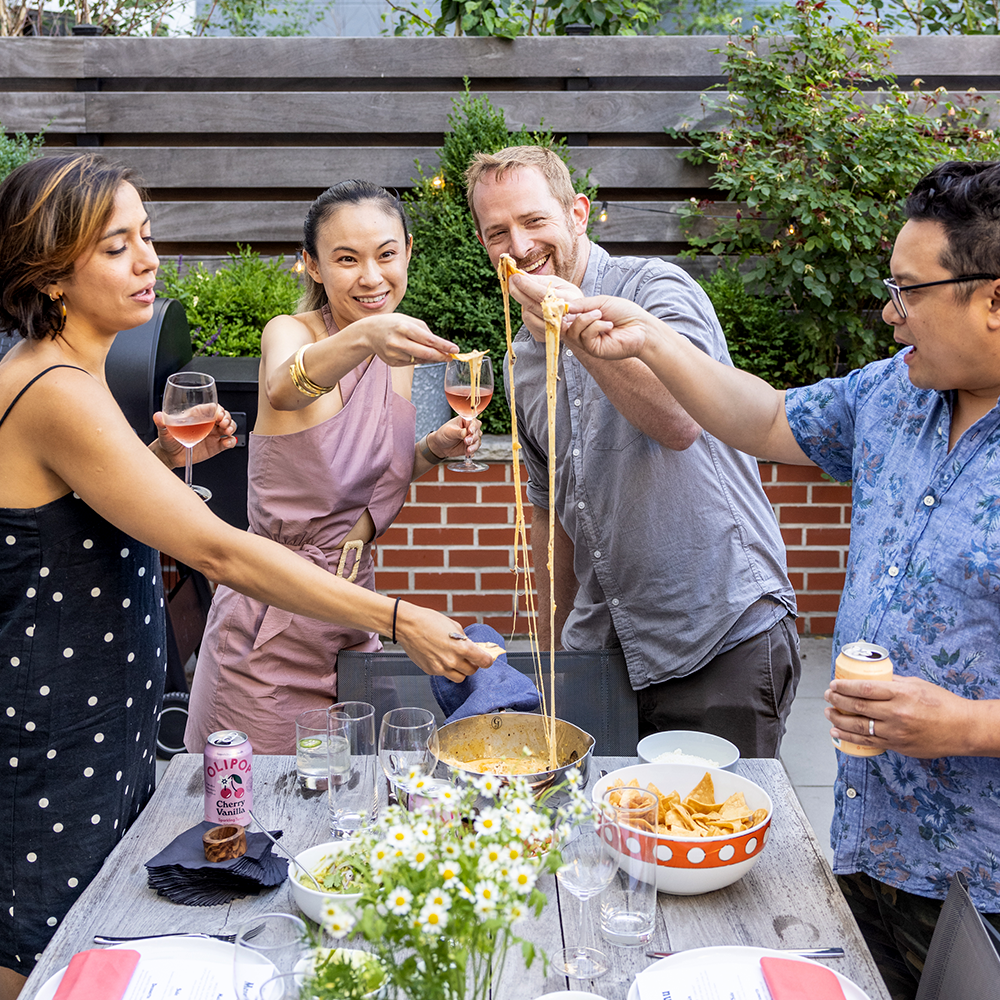 4 people enjoying food together at a BBQ