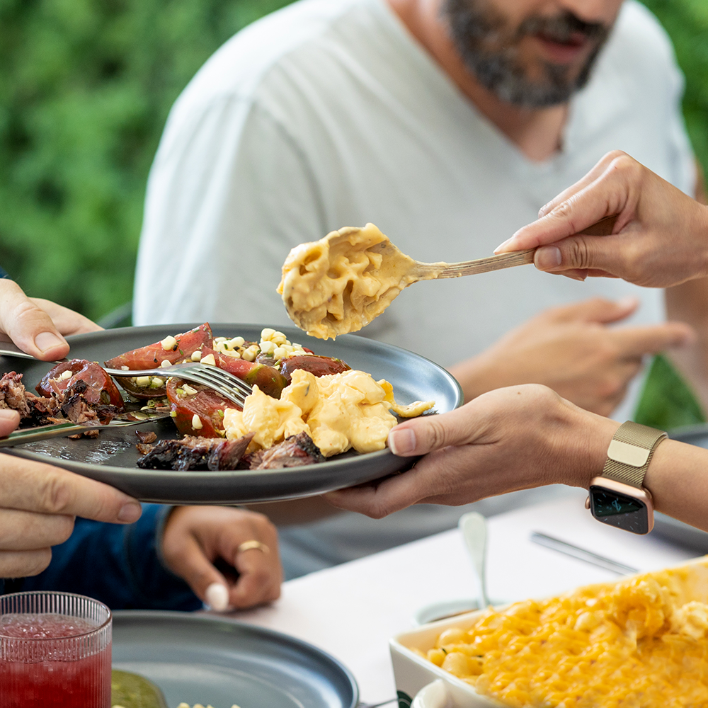 Placing food on a plate to share with others at a BBQ
