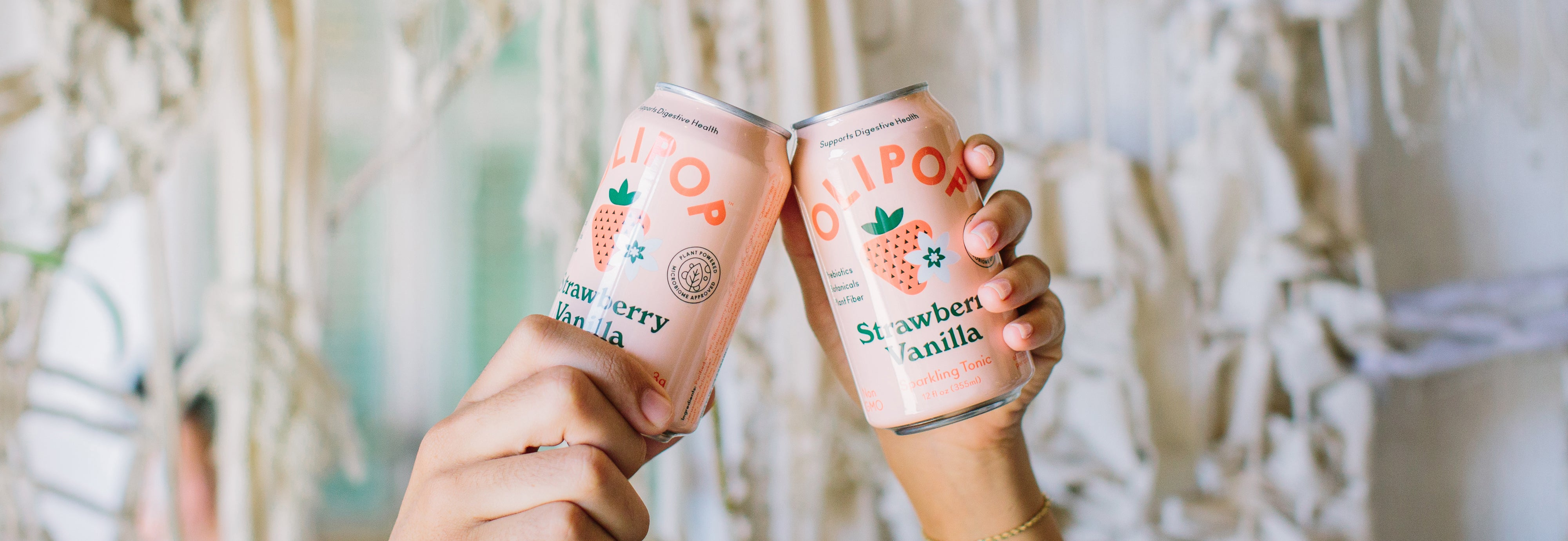 Hands holding two cans of Olipop strawberry vanilla