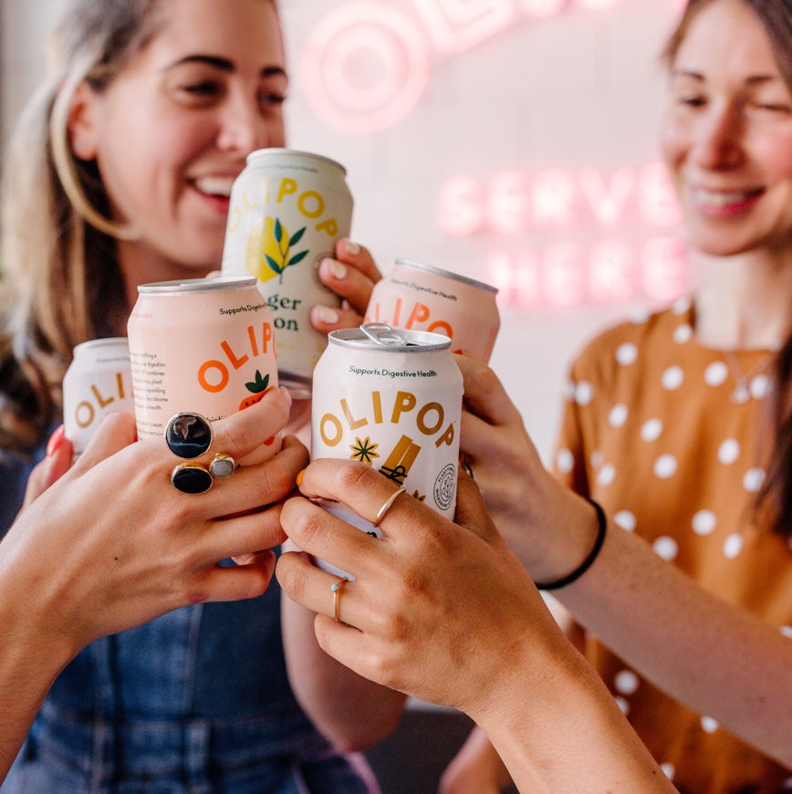 People cheers with Olipop cans