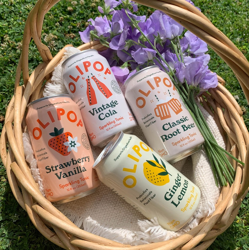 Wicker basket with Olipop cans and flowers inside