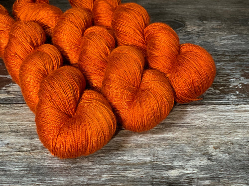 Three skeins of hand dyed yarn of baby camel and silk, in rich orange tones.