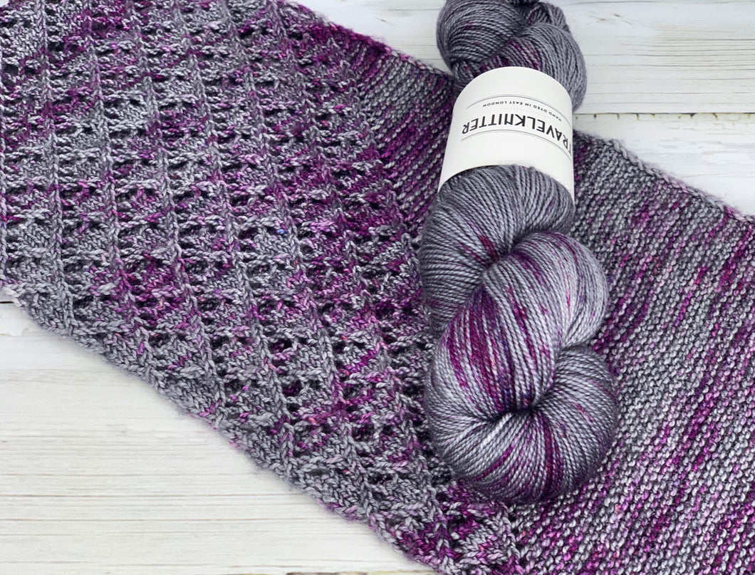 A skein of merino/silk yarn, hand dyed in a silver grey with magenta/purple speckles.  It is sitting on top of hand knitted cowl that shows the colours.