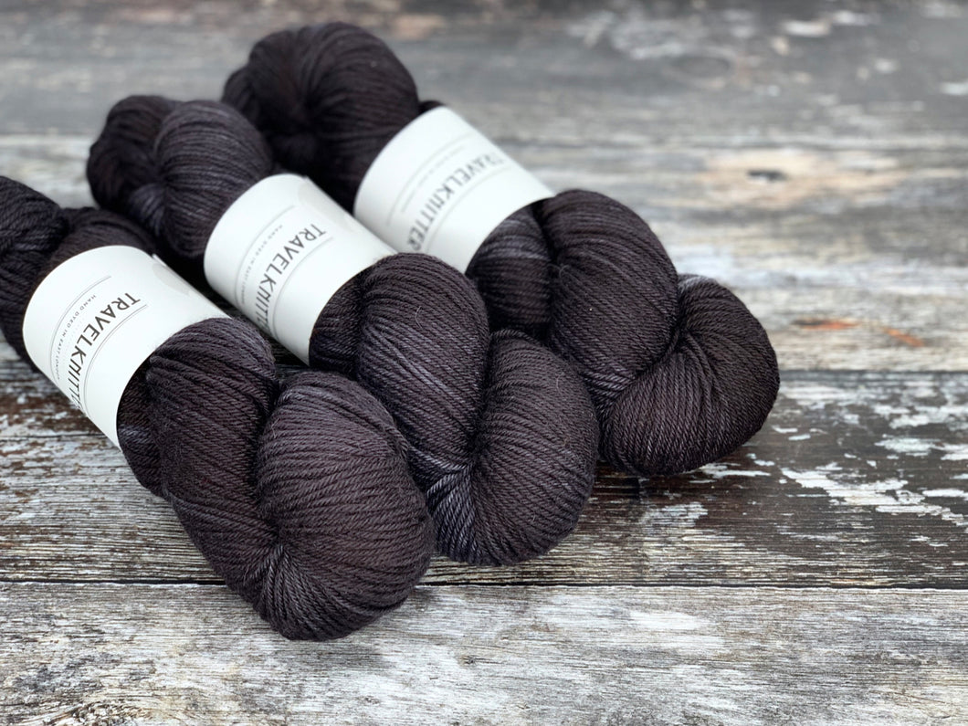 Three skeins of BFL DK weight hand dyed yarn, dyed in a black and charcoal tones.