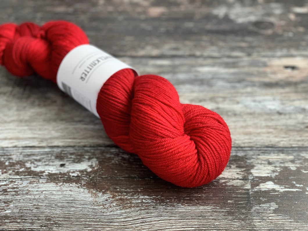 One skein of DK weight BFL yarn, in a rich red colour.
