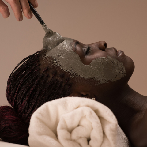 Black woman using powder face mask