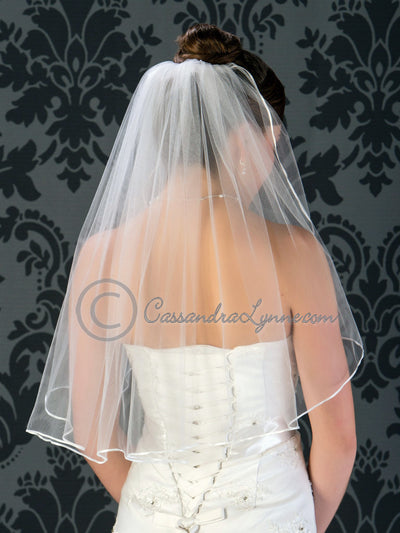 Elbow length wedding veil with satin ribbon edge.