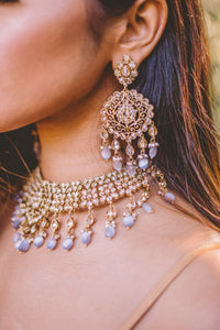 Gold tone necklace and earrings set studded with faux kundan and gray beads.